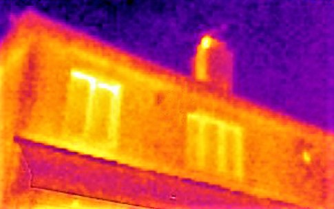 An image taken with a thermal imaging camera showing the chimney stack glowing as it is warmed by warm air from the home travelling up the chimney. A thin wisp of orange against purple graphically shows warm air escaping into the night air