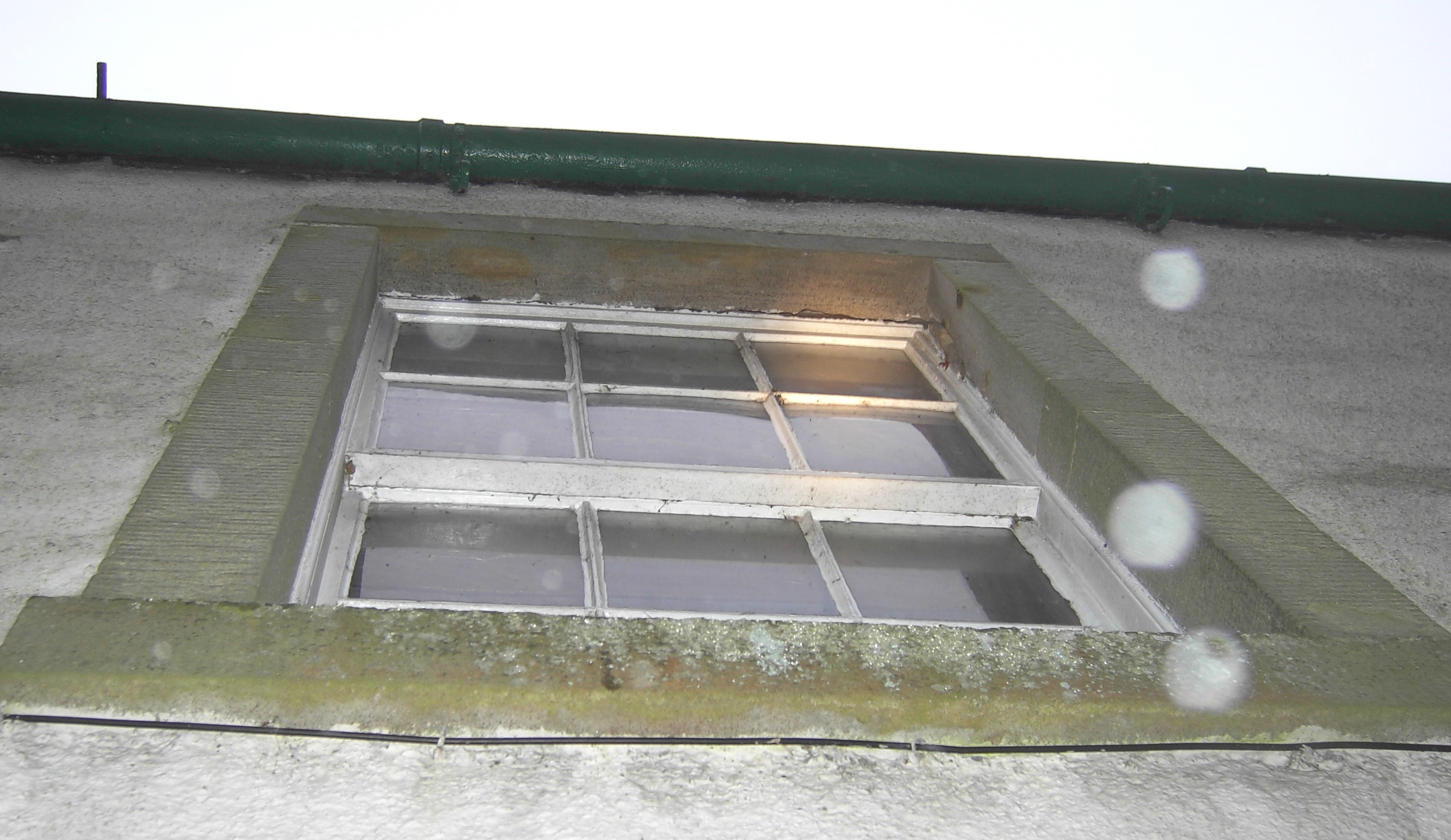 A sash window with sandstone lintel. The angle is from ground level looking up to a first floor window so gaps between the top lintel and the window casing can be seen
